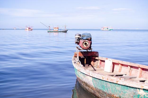 Старая лодка - рыбак, высадка на берег на размытом синем море и голубом небе