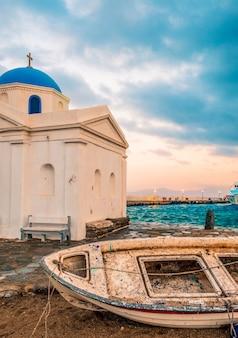 Старая лодка с греческой церковью на острове миконос на закате