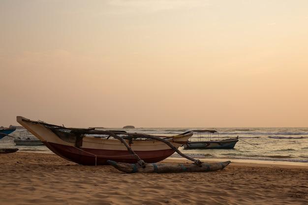 Старые лодки на берегу океана на закате
