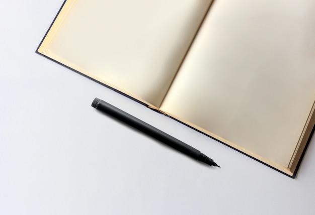 오래 된 책과 흰색 테이블에 검은 펜
