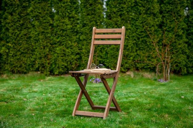 Старая книга и очки на деревянном стуле в саду весной