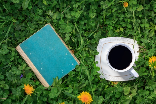 Old book and a cup of hot coffee on a green meadow summer or spring morning top view