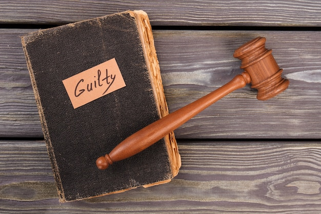 Old book gavel and guilty verdict. trial justice concept. top view flat lay.