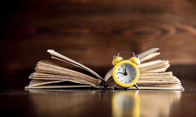 Old book and little alarm clock on wooden table