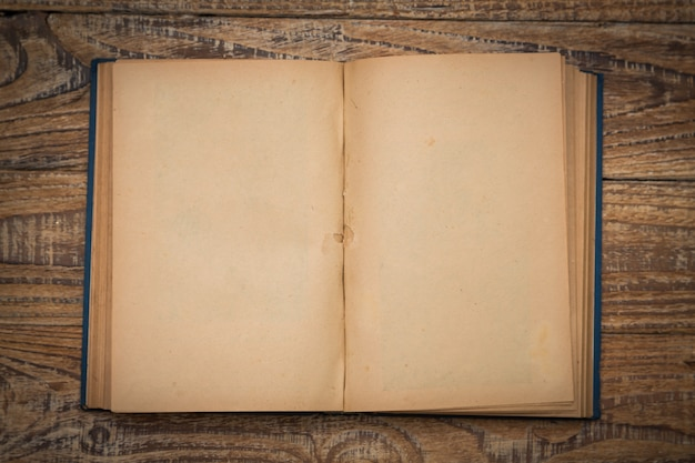 Старая книга открыта на деревянный стол вид сверху