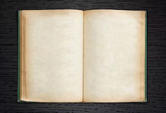 Old book open on dark wood background