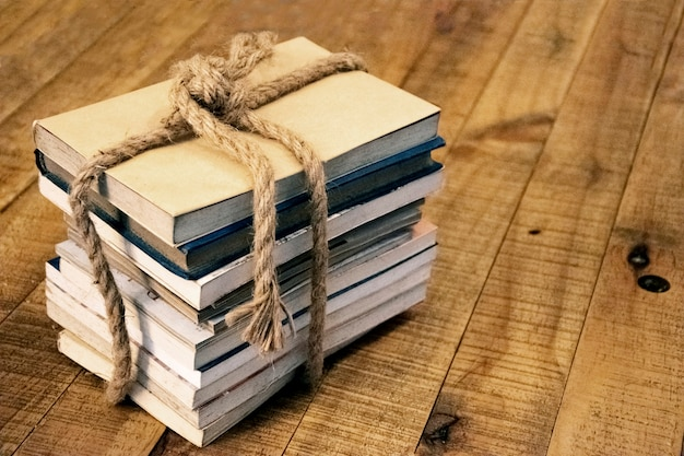 Old book tied with a thick rope on a wooden table