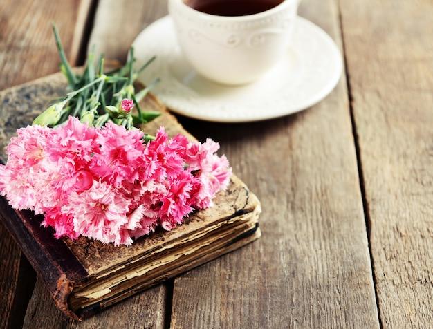 美しい花と木製のテーブルの上のお茶の古い本をクローズ アップ