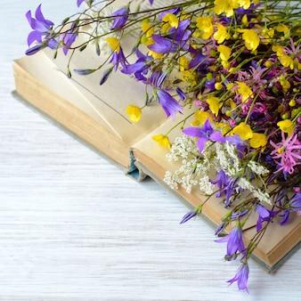 초원 꽃 향수 빈티지 배경의 꽃다발과 함께 오래 된 책
