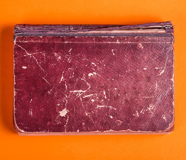 Old book with brown shabby cover on orange background