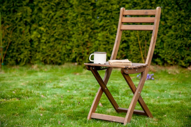 Old book with cup of tea on a table on green grass in spring