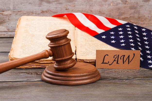 アメリカの法律の古い本。アメリカ合衆国の旗が付いている木製のガベル。