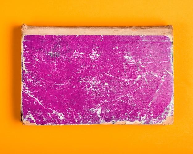 黄色の背景に紫色のぼろぼろのカバーと古い本