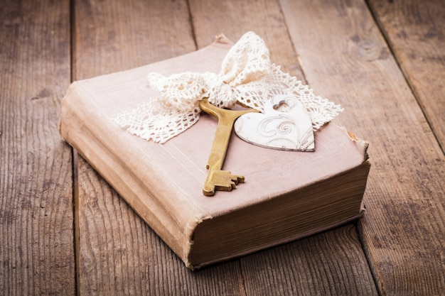 Старая книга со старинным ключом и деревянным сердцем, концепция воспоминаний