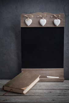 Old book and wooden blackboard
