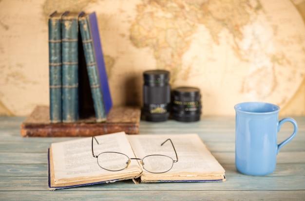 Старые книги, чашка горячего напитка, очки, объективы фотоаппаратов.