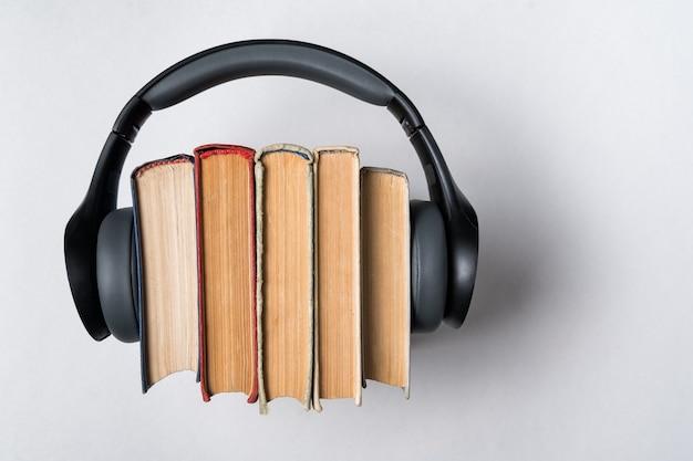 Старые книги и наушники на белом. аудиокниги аудио концепции библиотеки. вид сверху.
