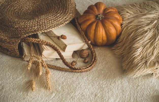 古い本とカボチャ、小麦、サイサリス、ドングリ、クルミの白い暖かい格子縞のヴィンテージストローバッグ。本と読書。秋の気分。秋の時間。