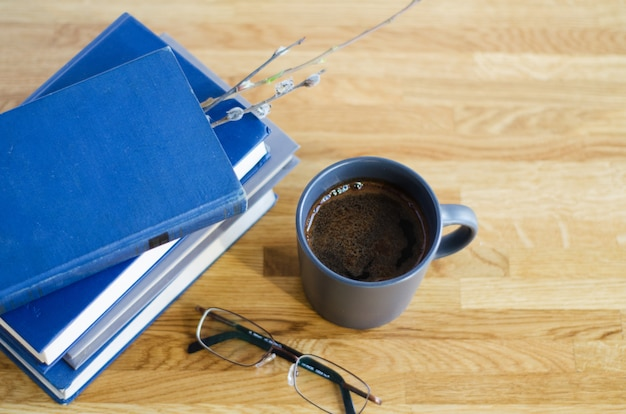 Old books are stacked on a wooden table. between the pages closed willow twig. on the table are soft focus glasses and a cup of coffee is standing.