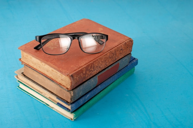 Old books and black glasses on a blue-green wooden.
