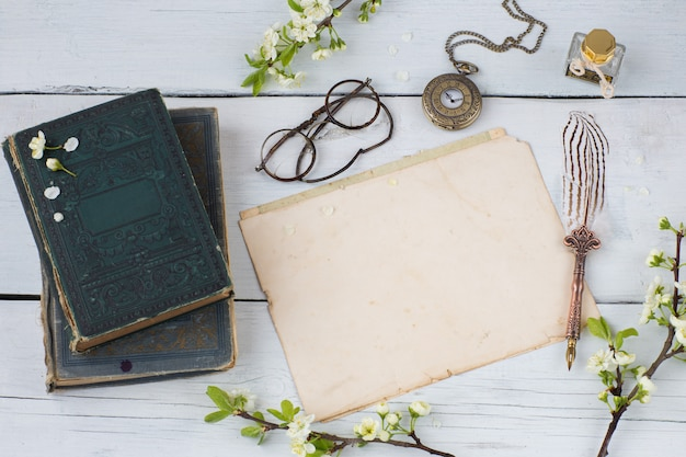 Old books, empty sheets of paper, fountain pen, glasses, pocket watches and branches of blossoming cherry