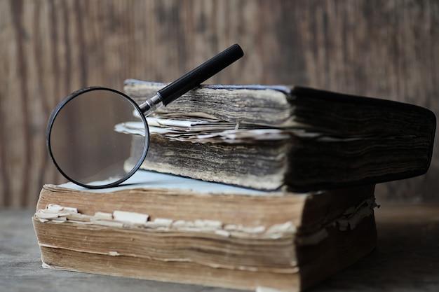 木製のテーブルとガラスの拡大鏡の古い本