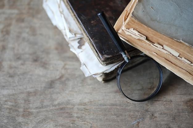 Старые книги на деревянном столе и стеклянной лупе