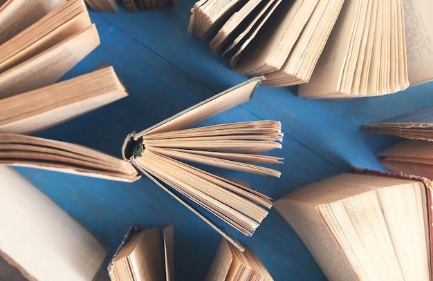 Старые книги на синем деревянном столе.
