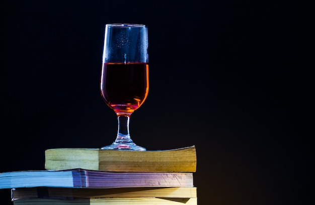 Old books overlap in a black background and with dim light one glass of red wine on top.