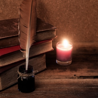 Old books, scrolls, feather pen and inkwell on wooden table
