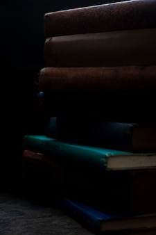 Old books stack on antique wooden surface in warm directional light