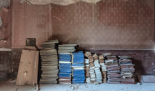 Old books stacked on the floor of an old abandoned house