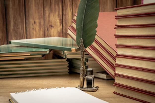 오래된 나무 탁자에 잉크와 메모장이 있는 오래된 펜이 어지럽게 쌓여 있는 오래된 책들