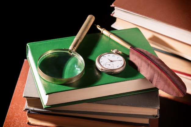 Old books with feather pen, magnifying glass and old vintage clock