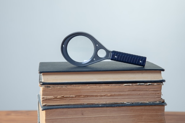 Old books with magnifying glass on the table