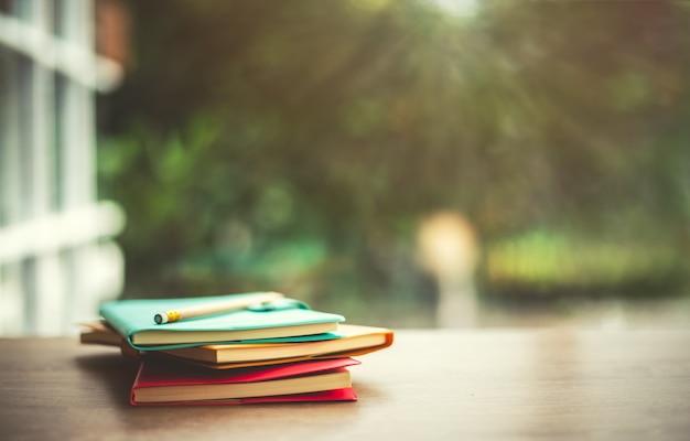 木製テーブルに鉛筆を置き、太陽の日のぼやけた背景を持つ古い本