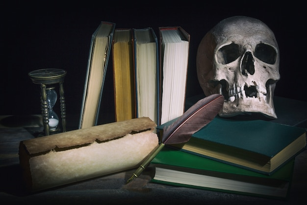 Old books with skull near scroll, quill feather pen and vintage hourglass.