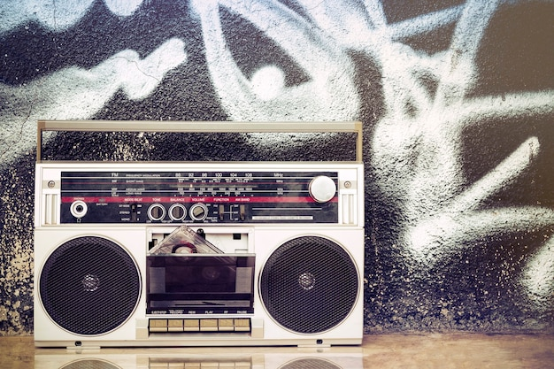 Old boombox with cassette on the floor and on a graffiti
