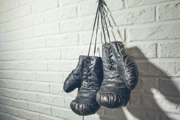 Старые боксерские перчатки висят на гвозде на кирпичной стене