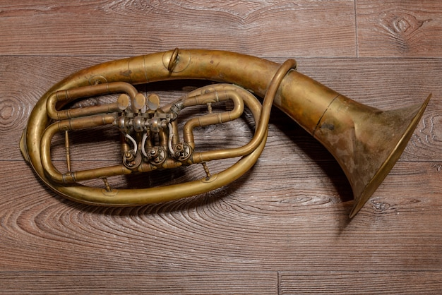 Old brass horn on wooden background