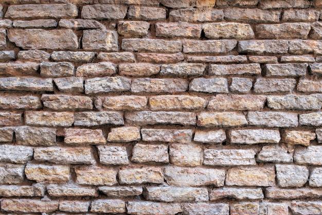 背景として古いレンガと石の壁。