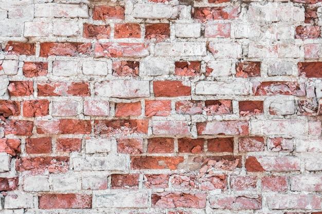 白灰色のコンクリートの要素で古い壁のテクスチャを壊す古いレンガ。