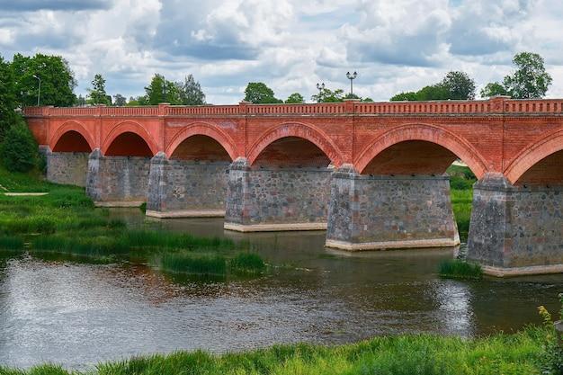Old brick bridge across the river venta in the city of kuldiga, latvia. cloudy day