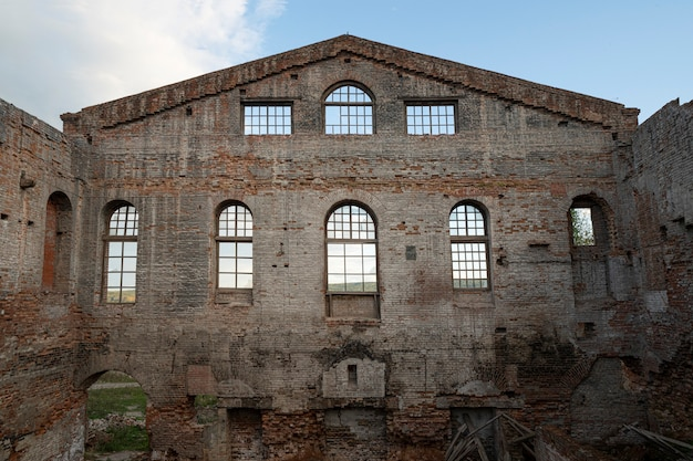 Старое кирпичное здание, фасадная стена. оконные арки,