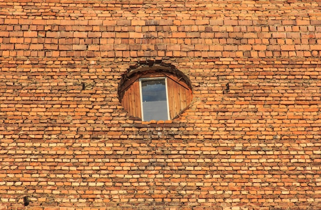 Old brick building with one window in the center