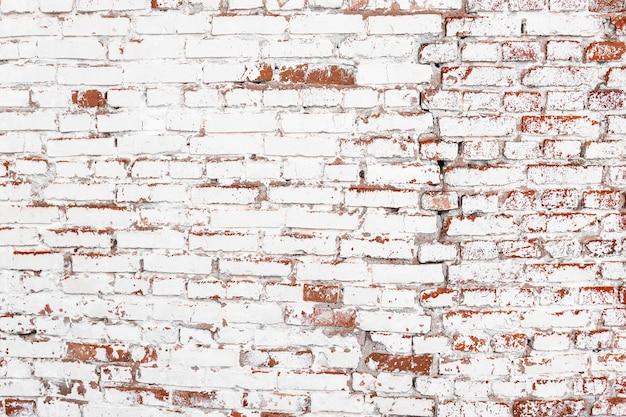 페인트와 큰 균열 벽돌로 덮인 오래된 벽돌 벽