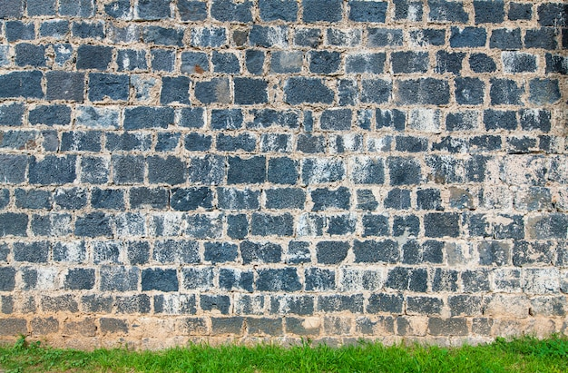 The old brick wall and green grass