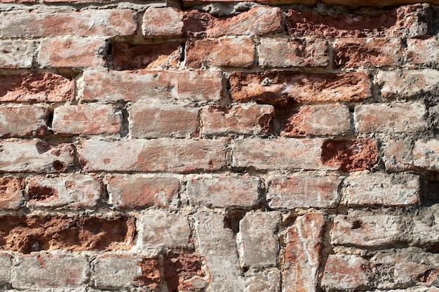 Старая кирпичная стена крепости, разрушенная или поврежденная во время боевых действий на войне