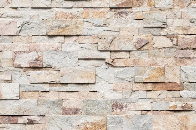 古いレンガの壁のテクスチャ、抽象的な石の背景。都会のレンガの壁、不均一な粗い石の壁。ベージュのタイル、花崗岩。