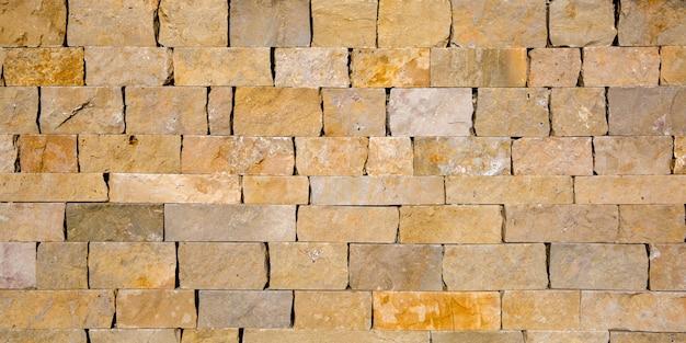 古いれんが造りの壁テクスチャシームレスな背景黄色の自然な砂岩タイルを一緒にステッチ